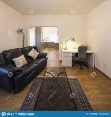 wohnzimmer mit schwarzem ledernem sofa und parkett stockfoto