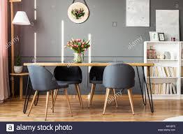 esstisch aus holz grau stühle bücherregal und rosa tulpen