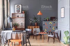 graue esszimmer interieur mit tisch stühle len pflanzen ecke holzschränke und konfetti auf der mauer sitzend stockfoto und mehr bilder alt