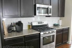 Dark cabinets white subway tile back splash medium toned granite