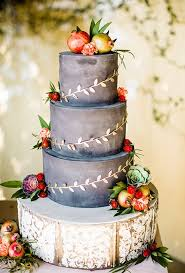 A Rustic Three Tiered Wedding Cake Adorned With Fruit And Gilded Ivy By