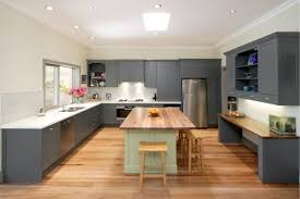 U Shaped Kitchen Design With Dark Grey Cabinet And White Countertop Using Wood Flooring