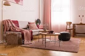 elegante wohnzimmer interieur mit trendigen grauen sofa mit pastell rosa kissen und decke burgund hölzernen kaffeetische daneben stockfoto und mehr