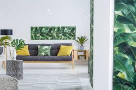 gelbe kissen auf schwarzem sofa im modernen wohnzimmer mit grünen blättern poster auf weiße wand und pflanze auf holzschrank