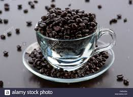 Transparent Glass Cup Filled With Coffee Beans On Dark Wooden Background