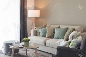 moderne wohnzimmer mit grünen kissen auf gemütliches sofa und holzle innenarchitektur