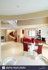 moderne esszimmer mit glastisch und blick auf wendeltreppe