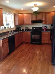 Wooden Kitchen Cabinets And Floor With Black Appliances Design