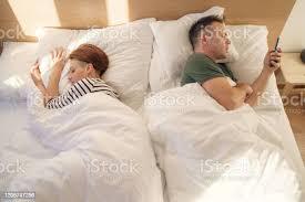 sly freund oder ehemann mit handy im bett während seine freundin schläft junger mann sendet heimlich sms per smartphone und betrügt seine frau die im