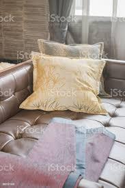scharlachrote stoff auf leder sofabett mit gelben kissen im wohnzimmer stockfoto und mehr bilder bettsofa
