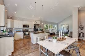 Interior Of Kitchen And Dining Room With High Vaulted Ceiling White Cabinetry Steel