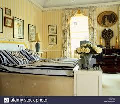 gelb gestreifte tapete und floral gardinen im schlafzimmer