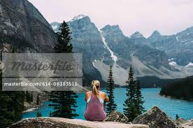Rear View Of Mid Adult Woman On Cliff Edge Looking At Alevated Moraine Lake