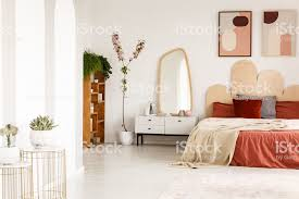 poster über rote bett mit decke innen geräumiges schlafzimmer mit spiegel und pflanzen echtes foto stockfoto und mehr bilder arkade