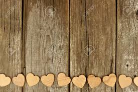 Valentines Day Wooden Hearts Forming A Bottom Border On Rustic Wood Background Stock Photo