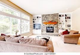ein großes helles wohnzimmer mit kamin und beige sofas ein