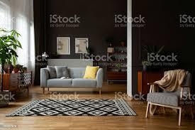echtes foto freiflächen dunklen wohnzimmer interieur mit formteil und poster an wand gemusterten teppich lounge kissen mit retromöbeln stockfoto