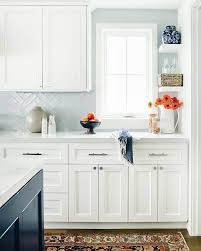 light blue herringbone tiles with white cabinets transitional