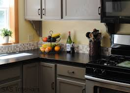 black kitchen cabinets with light countertops and photos