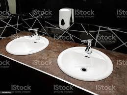 badezimmer interieur in schwarz und weiß runde keramik waschbecken spiegel kunststoff seife teller und chrom armaturen zum händewaschen nach der