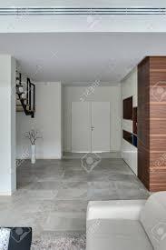 mit hellen wänden und hellen fliesen auf dem boden vorne gibt es ein helles sofa und einen dunklen tisch auf dem teppich auf der linken seite