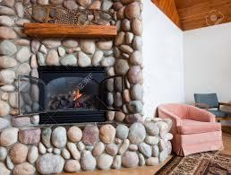 ein gas kamin in bunten fluss felsen mit einem hölzernen mantel gesetzt gekrönt mit vintage schneeschuhen in einem weißen wohnzimmer mit stühlen und