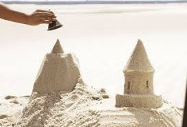 Hand Using A Funnel To Build Sandcastle Tower