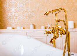foto auf lager reichhaltiger goldener wasserhahn und weißes bad im badezimmer