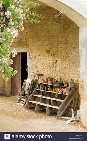 Terracotta Flower Pots On Rustic Wooden Steps Against Wall In Arched Courtyard Of French Country House With Pink Climbing Roses