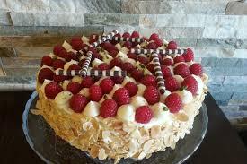 weiße schoko torte mit himbeeren dekoriert und mit schoko