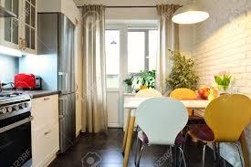 innenraum der küche im skandinavischen stil mit weißen möbeln und einem esstisch