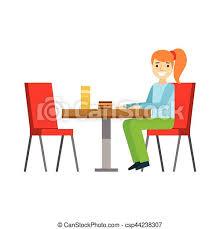 ein mädchen das am tisch sitzt und einen kuchen isst