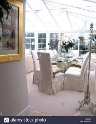 stühle mit weißen losen abdeckungen an glas tisch im