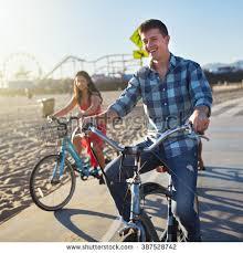 Man With Friends Riding Bikes On Bike Path At Santa Monica Beach