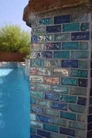 """Iridescent blue 1"""" X 2"""" glass tile surrounds the pool and raised"""