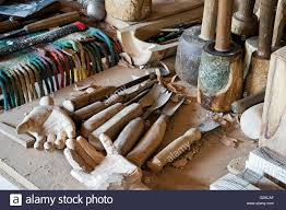 carved wooden hands and chisels plus woodworking tools in a wood