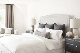 Chic Bedroom Features A Gray Linen Camelback Headboard On Bed Dressed In Black Pinstripe Pillows Flanked By Nightstands Topped With Birch Wood Lamps