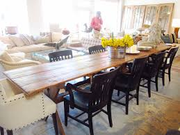 Long Farmhouse Dining Table Made From Reclaimed Wood With Flower Centerpieces And 8 Black Wooden Chairs 2 White Fabric Cover