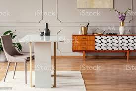 marmortisch neben einem stuhl in einem eklektischen esszimmerinterieur mit einem retroschrank stockfoto und mehr bilder blume