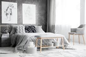 geräumiges schlafzimmer mit sessel knotenkissen auf dem bett und zwei postern an strukturierter wand