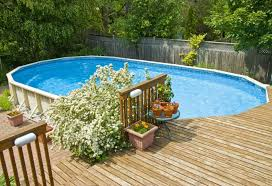 An Oval Shape Above The Ground Swimming Pool And Wooden Deck