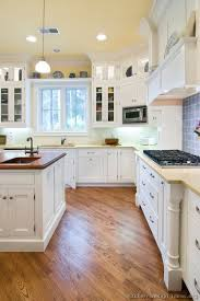 A Lovely Cottage Kitchen With White Cabinets Wood Floors And Beautiful Hood