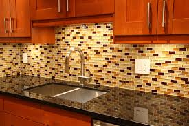 A Glass Tile Backsplash With Accents Of Gold And Red
