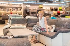 kaukasischen frau einkaufen für möbel sofa und wohnkultur im laden sitzt auf vorstellen ihre neue heimat architektonische anordnung