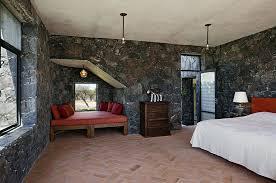Mediterranean Bedroom Showcases Terracotta Tiles And Dark Stone Walls