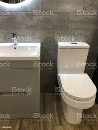 bild modernen badezimmersuite mit boden weiße toilette weiche enge toilette sitzdeckel waschbecken schranktüren schubladen waschbecken und mixer