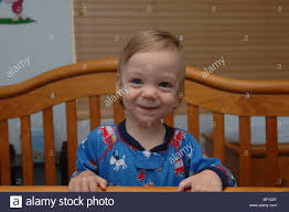 A Very Happy Young Blond Boy Stands In His Crib Smiling And Laughing ...