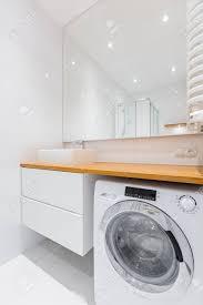 weißes badezimmer mit holzarbeitsplatte waschbecken schrank spiegel und waschmaschine