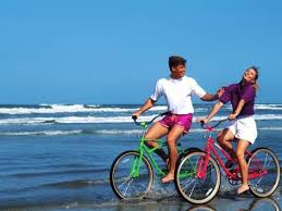 Middle Aged Couple Riding Bikes On The Beach