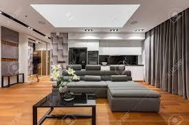 wohnzimmer mit grauem schmalem sofa schwarzem tisch und küchenzeile
